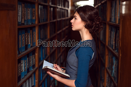 girl with notebook select textbook in