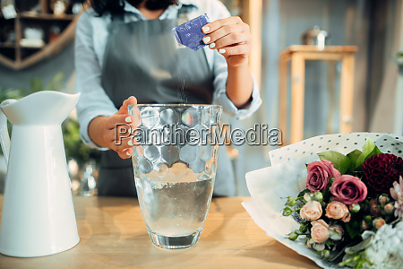 florist adds fertilizer to the water