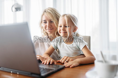 smiling mother and child uses laptop