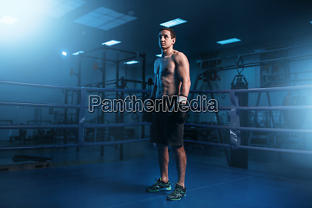 muscular boxer in black gloves on