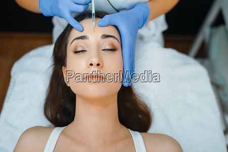 cosmetician gives face botox injections to