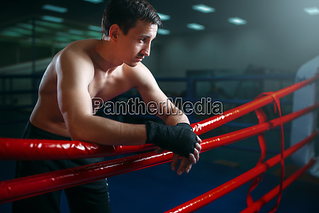 boxer in black bandages poses on