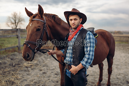 cowboy, poses, with, horse, on, texas - 28061694