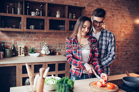 husband, hugs, wife, while, she, cooking - 28061768
