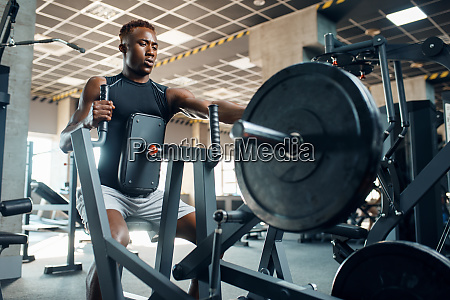muscular, sportsman, at, exercise, machine, in - 28061420