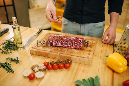 male person sprinkles raw meat with