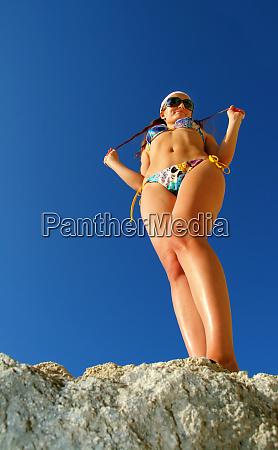 playful tan girl on rock