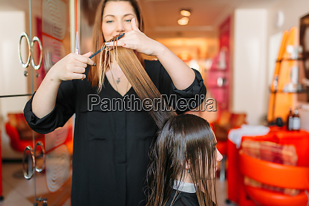 female hairstylist runs the comb hairdressing