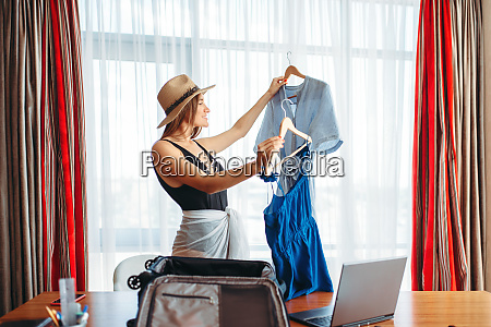 woman selects outfits thinking about voyage