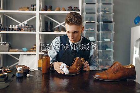 shoemaker polishes the shoe footwear repair