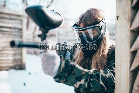 female paintball player with marker gun