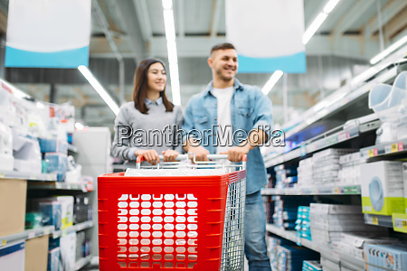 smiling couple with trolley in market