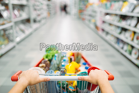 female person hands drags the cart