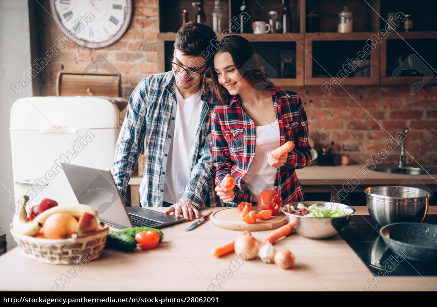 couple, looks, at, a, recipe, in - 28062091