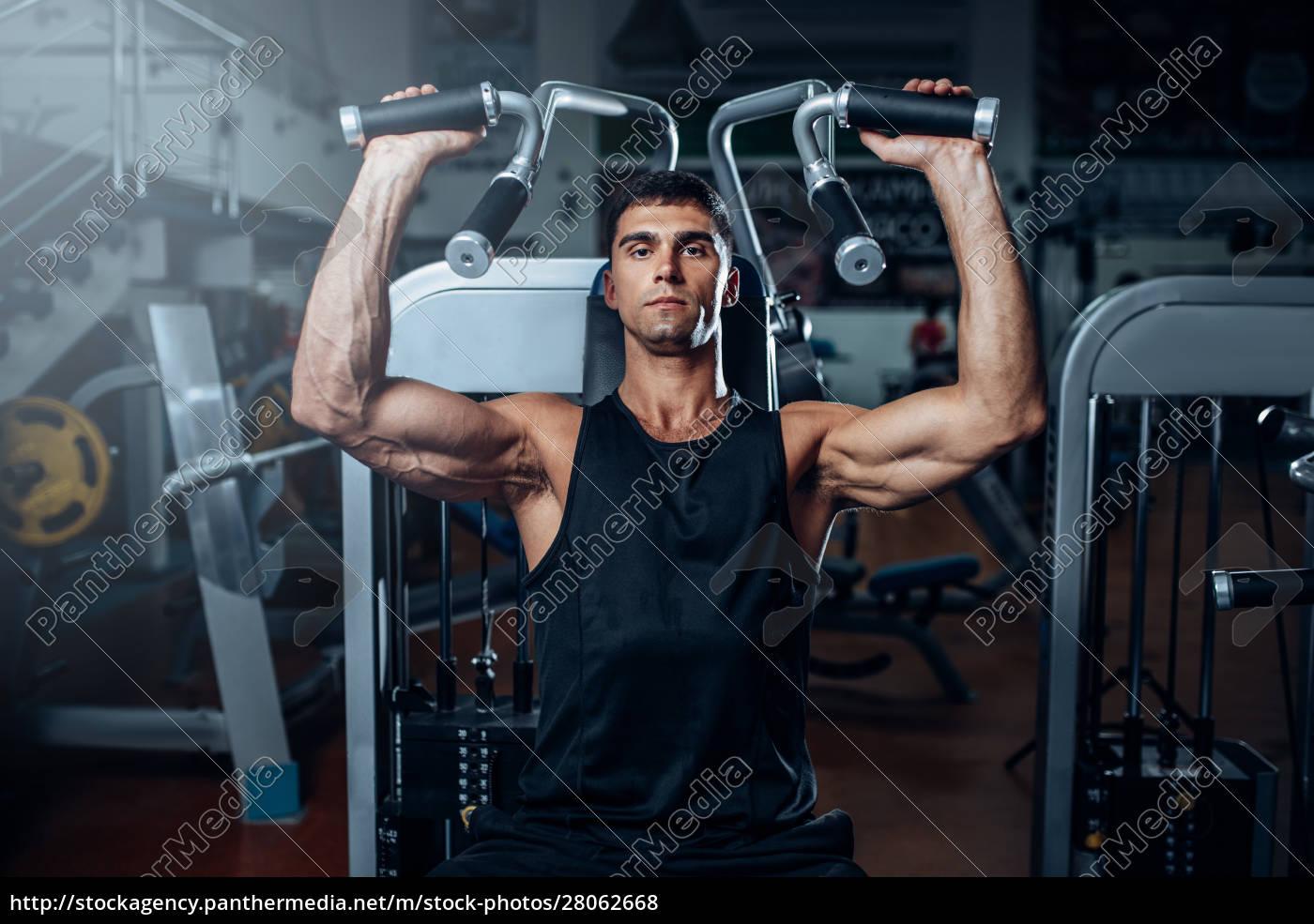 tanned, man, training, on, exercise, machine - 28062668