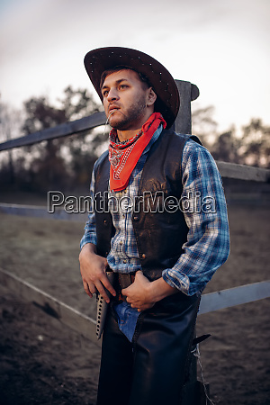 young, cowboy, poses, against, horse, corral - 28062420