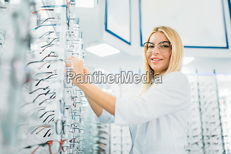 female optician shows glasses in optics