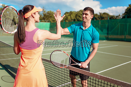 happy couple with rackets on outdoor