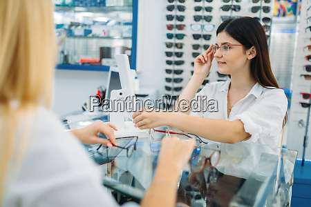 female optician and consumer chooses glasses