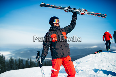 skier holds skis and poles in