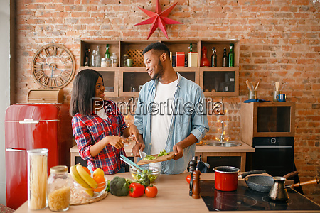 playful, black, couple, cooking, dinner, on - 28063121