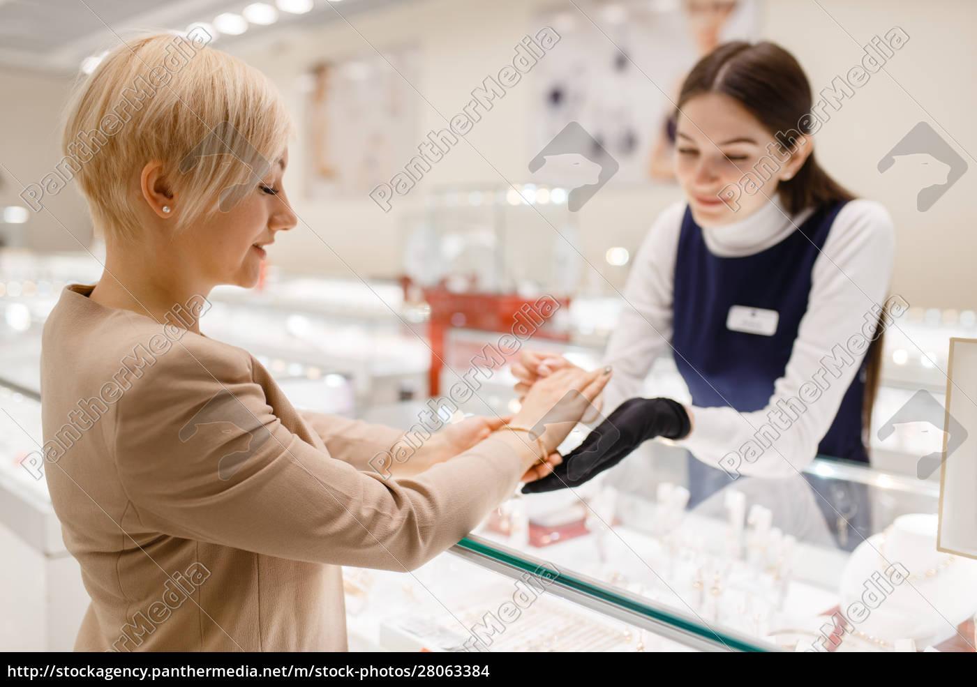 woman, trying, on, gold, bracelet, in - 28063384