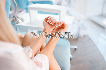 female customer shows nails in beauty