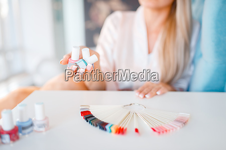 female customer holds nail varnish bottles