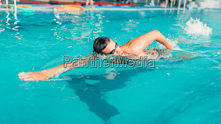 swimmer in glasses swims in indoor