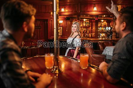 friends clinking mugs waitress on background