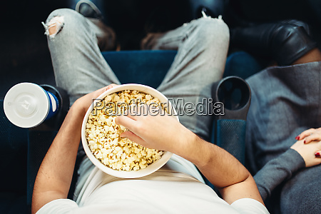 male person with popcorn in cinema