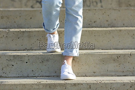 woman legs wearing sneakers walking down
