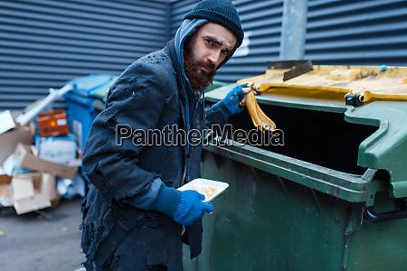 male bearded beggar searching food in