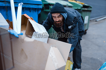 bearded homeless searching food in trashcan