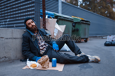 dirty beggar with food sitting at