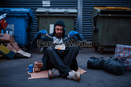 dirty beggar with knife and fork