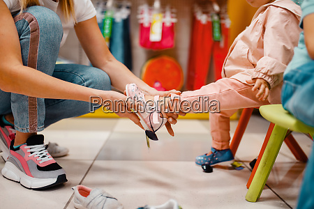 mother with girl choosing shoes in