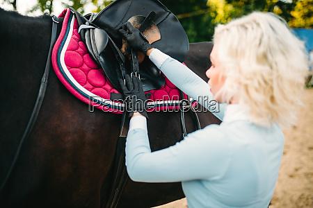 female rider preparing a horse saddle