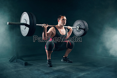 powerlifter in sportswear doing squat with