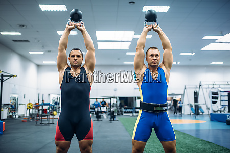 male lifters lifted kettlebells over thier