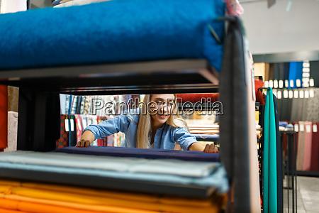 saleswoman measures fabric view through shelf