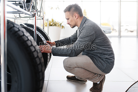 man choosing tyres for new car