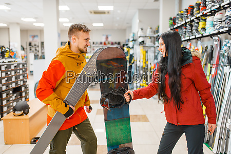 couple buying downhill ski and snowboard