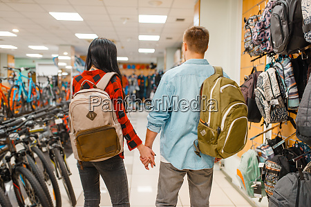 couple trying on backpacks shopping sports
