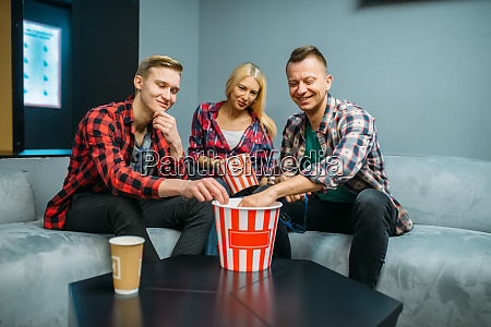 friends eating popcorn in cinema hall