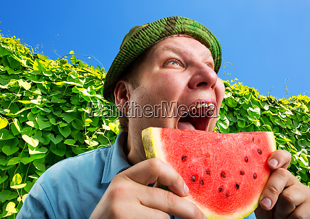 bizarre man eating watermelon