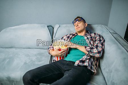 male spectator sleeping on sofa in