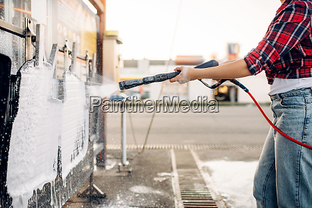 female person with water gun cleans