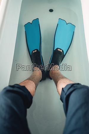 businessman in flippers sitting in bathtub