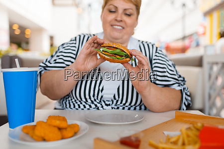 fat woman eating fastfood in mall